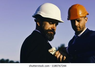 Constructors make deal. Bribery, business and corruption concept. Managers wear smart suits, ties and hardhats on blue sky background. Man with beard and sly face gives bribe.