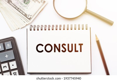 CONSULT - text written on a notebook with office background.