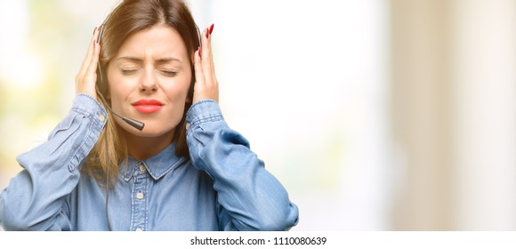 Consultant of call center woman in headphones covering ears ignoring annoying loud noise, plugs ears to avoid hearing sound. Noisy music is a problem.