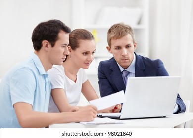 Consultant with a couple looking at laptop