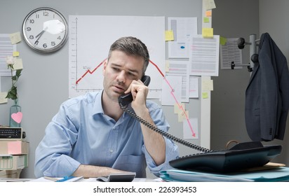 Consultant on the phone with negative business chart on background.