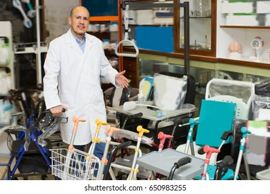 Consultant posing near display with orthopaedic equipment and machines
