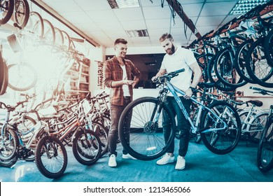 Consultant Shows Bicycle to Client in Sport Shop. Portrait of Young Shop Assistant Wearing White T-Shirt Helps in Mountain Bike Choosing. Happy Salesman in Sport Store with Row of Bikes on Backround