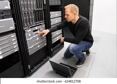 It consultant work with laptop in datacenter