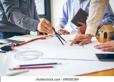 Consultation between colleagues, engineering team to check the blueprint used to build commercial buildings for joint ventures.
