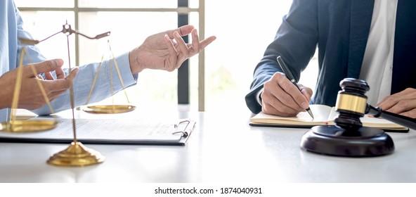 Beratung und Konferenz von professionellen Geschäftsfrau und männlichen Anwälten, die in der Kanzlei arbeiten und diskutieren. Rechtskonzepte, Richter mit Maßstäben der Gerechtigkeit.