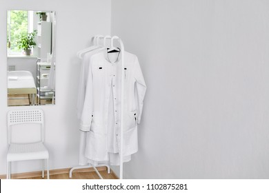 Consulting or cosmetology room. Mirror, chair, hanger with doctor's dressing gowns. Interior with white walls.