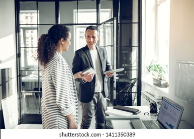 Consulting trainee. Interior designer consulting his young trainee while telling her some information