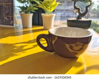 The consumed coffee was laid on a yellow wooden table.