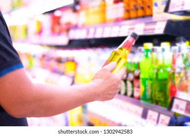 Consumer choosing beverage from shelf in Supermarket, looking for favorite drinking with no ingredient alcohol and sugar. Many brand of beverage bottles on shelves selling in superstore.
