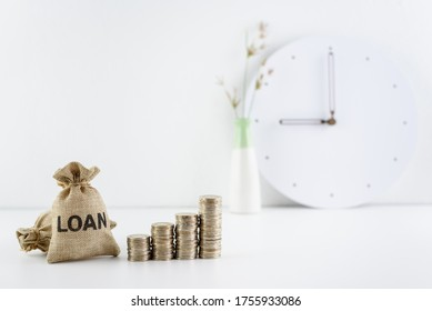 Consumer loan refinance, financial concept : Loan bags, row of rising coins on a table, depicts business or debtor revises interest rate, repayment period or credit agreement to save on debt payment. - Shutterstock ID 1755933086