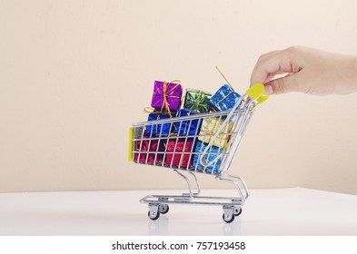 consumer and shopping concept, cropped hand push supermarket trolley