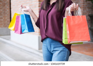 Consumer and shopping lifestyle concept, Happy young woman standing and holding colorful shopping bags enjoying great day in shopping.