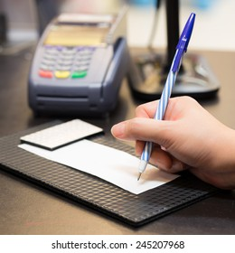Consumer signing on a sale transaction receipt with Credit Card Machine in Background