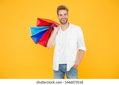 Consumerism concept. Big discount. Great choices great purchases. Happy man holding purchases in paper bags. Cheerful client customer consumer smiling with fashion purchases. Impulse purchases.