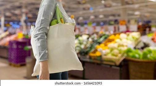 消費主義、食べ物、環境に優しいコンセプト – スーパーの背景に食べ物の買い物用に白い再利用可能なキャンバス袋を持つ女性