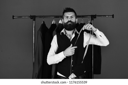 Consumerism and elegance concept. Man with beard in vest by clothes rack. Businessman with confident face near jackets on blue background. Shop assistant or seller with measuring tape in hands