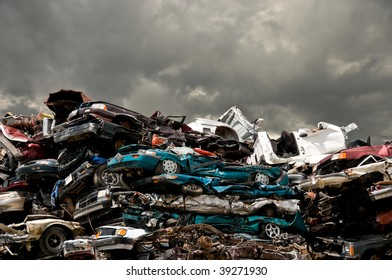 consumerism seen in a huge pile of wrecked vehicles under foreboding stormy sky