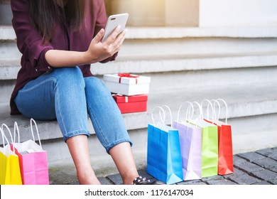 Consumerism, shopping, lifestyle concept, Young woman sitting near shopping bags and gift box while playing smartphone enjoying in shopping.