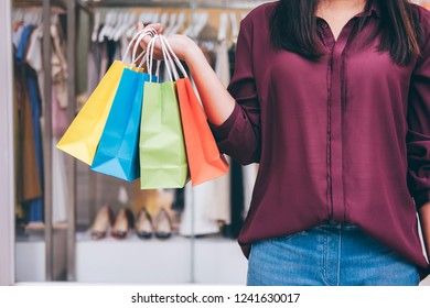 Consumerism, shopping lifestyle concept, Young woman standing and holding colorful shopping bags enjoying in shopping.