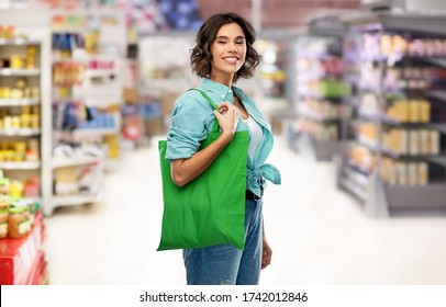 consumerism, sustainability and people concept - portrait of happy smiling young woman in turquoise shirt with green reusable canvas bag for food shopping over supermarket or grocery store background