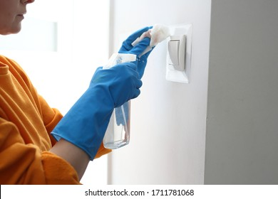 Contact disinfection, disinfection of switches. Prevention and prevention of infection. The woman disinfects the light switches.