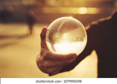 Contact juggling. Man balancing glass bowl on hand. Inverted reflection of person in ball. Mastery of representation. Picture at sunset. Trend view