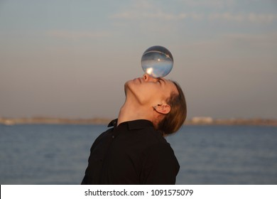 Contact juggling. Man balancing a glass bowl on his head. Reflection of setting sky and river in ball. Mastery of representation. Trend view