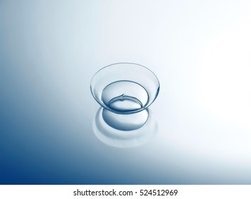 Contact lens on smooth light background, close up view. Medicine and vision concept