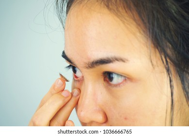 Contact lens for vision. Closeup of female face is applying contact lens on her eyes