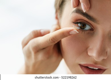Contact Lens For Vision. Closeup Of Female Face With Applying Contact Lens On Her Brown Eyes. Beautiful Woman Putting Eye Lenses With Hands. Opthalmology Medicine And Health. High Resolution