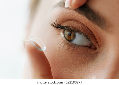 Contact Lens For Vision. Closeup Of Female Eye With Applying Contact Lens On Her Brown Eyes. Beautiful Woman Putting Eye Lenses With Hands. Opthalmology Medicine And Health. High Resolution