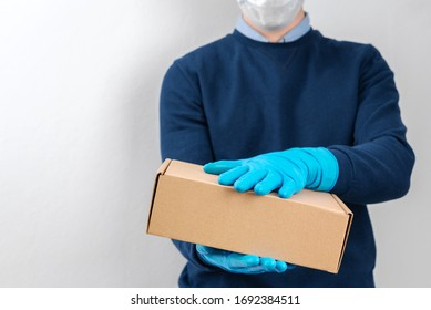 Contact less delivery concept, safe shipment, courier in a protective mask and rubber gloves with carboard box , order from online shop, copy space.