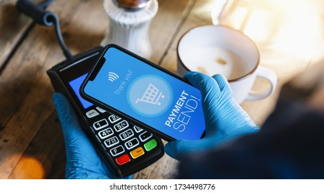 contact less payment on a mobile phone. Close up of a woman hand with gloves paying contactless with a smartphone screen application. Hand holding smart device to pay. Mockup cellphone screen.