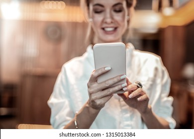 Contact with me. Pleased woman keeping smile on her face while typing message