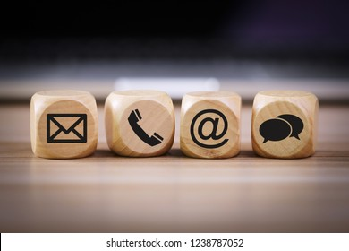 Contact Methods. Close-up of a phone, email, chat and post icons wooden block.