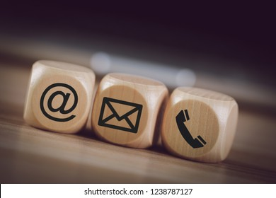 Contact Methods. Close-up of a phone, email and post icons wooden block.