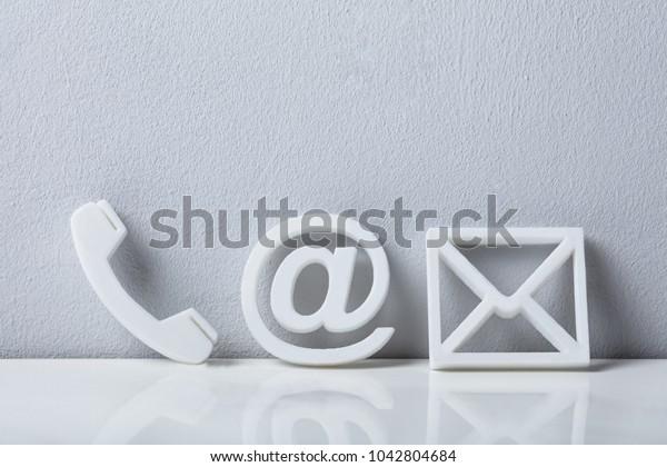 Kontaktmethoden. Nahaufnahme eines Telefons, E-Mail und Postsymbole, die auf der weißen Mauer stehen