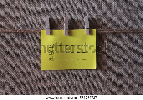 Contact symbol written on a wooden table and paper sticky notes.