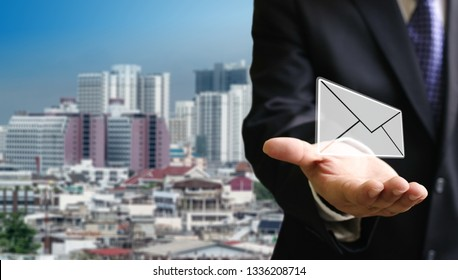 Contact us concept, Businessman carry email in hand with cityscape background
