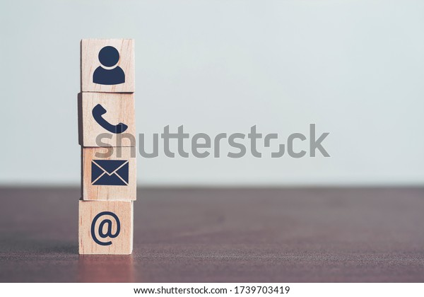 Contact us concept, Profiles and detailed personal information to identify yourself. Wooden blocks in his hand with icon telephone, mail and email, Online business communications concept, copy space