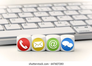 Contact us concept with red, yellow, green and blue icon on cubes in front of a keyboard