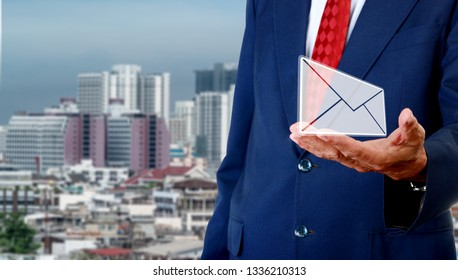 Contact us concept, Senior businessman carry email in hand with cityscape background