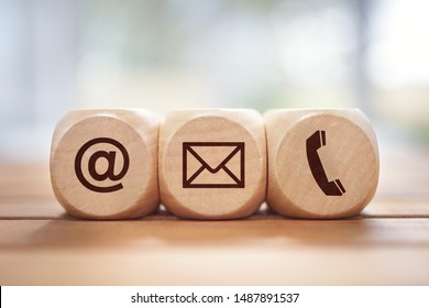 Contact us concept with wood block and symbols at, e-mail address and phone