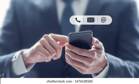 CONTACT US, Hand of Businessman holding mobile smartphone with ( mail,phone,email ) icon. customer support concept, copy space.