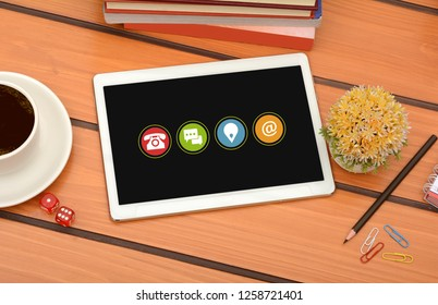 Contact Us Icons on tablet with coffee cup and office supplies