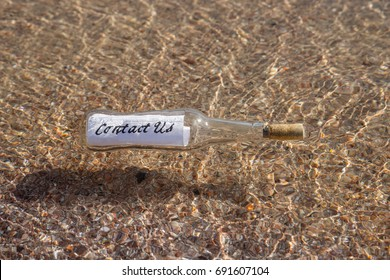 Contact us message in a Bottle floating in water over sandy bottom