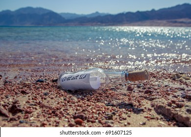 Contact us message in a Bottle on a beach with water and mountain background