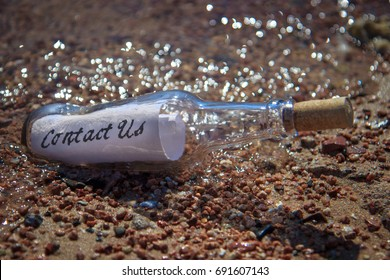 Contact us message in a Bottle on a beach