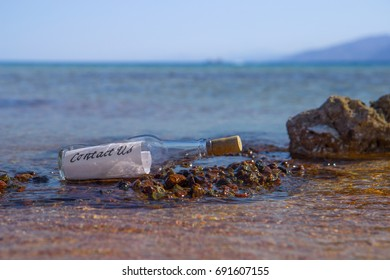 Contact us message in a Bottle on a beach with blue water background